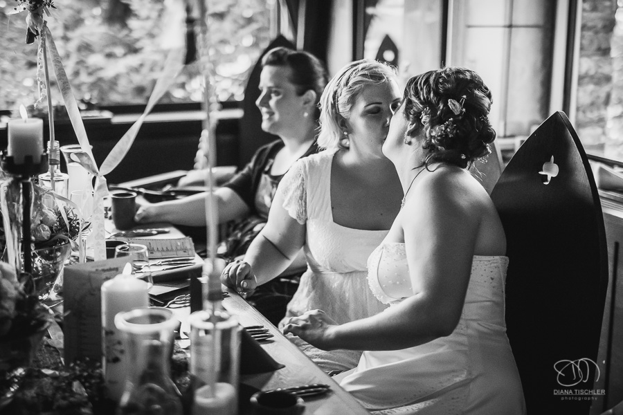 Brautpaar zwei Frauen Kuss am Tisch bei der Hochzeitsfeier