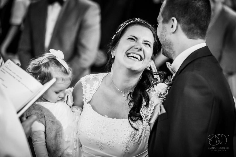 Brautpaar lachend mit Kind in der Kirche Trauung