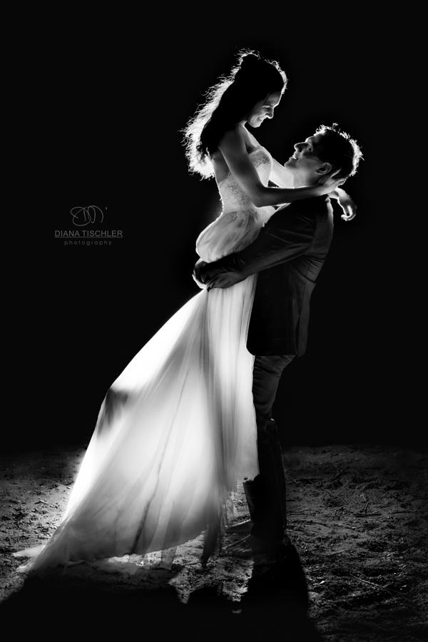 Brautpaar nachts beleuchtet er hebt Braut hoch lachend leuchtendes Kleid