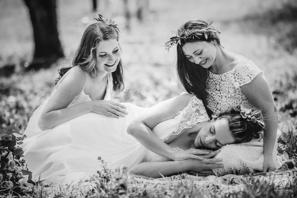 Bräute lachen zusammen auf einer Wiese im Frühling Leistungen Hochzeitsfotograf