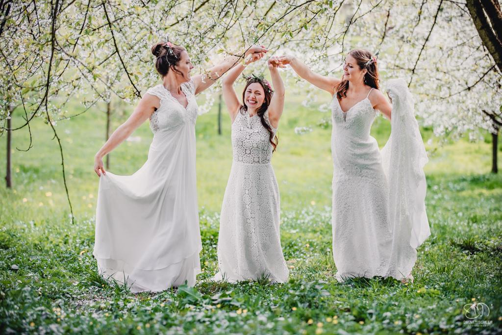 Braut Freundinnen auf Wiese unter Kirschbaum Blueten