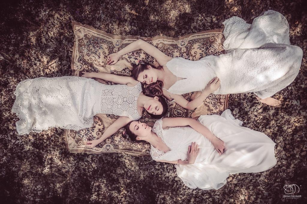 Braut Freundinnen liegen auf Wiese unter Kirschbaum