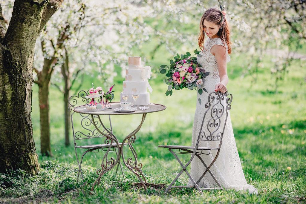 Braut an vintage Tisch mit Hochzeitstorte auf Wiese unter Kirschbaum