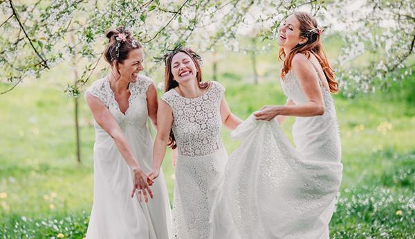 Freundinnen lachend auf Wiese unter Kirschbaum mit Brautstrauss
