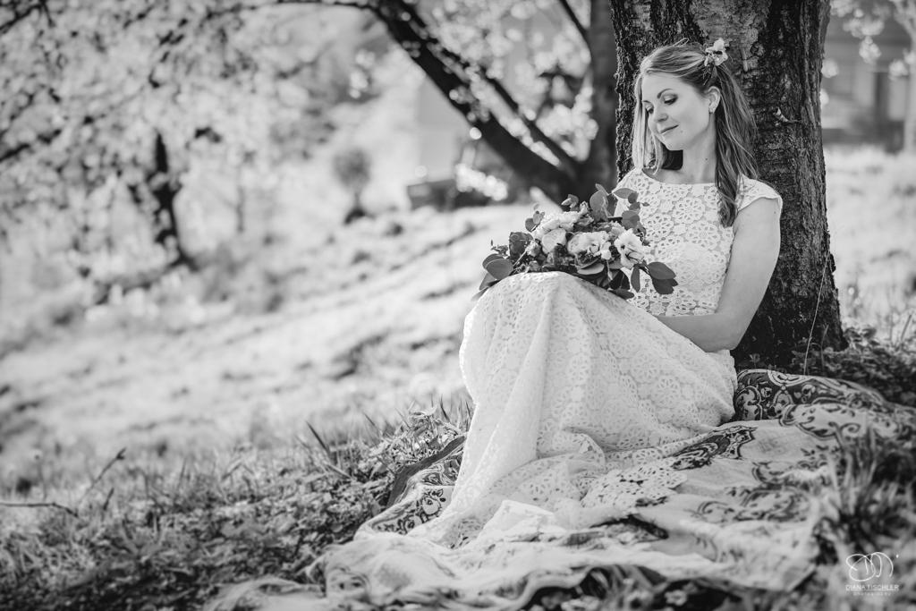 Braut sitzt unter einem Baum auf einer Wiese im Frühling Leistungen Hochzeitsfotograf
