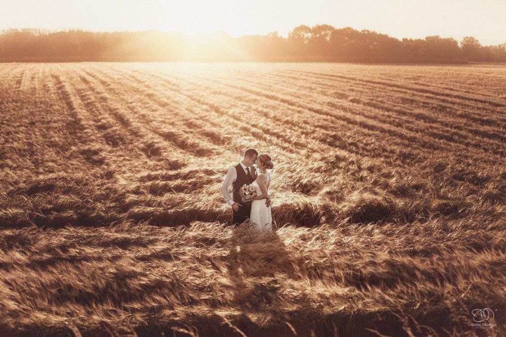 Brautpaar im Feld in tollem Licht bei Sonnenuntergang lachend