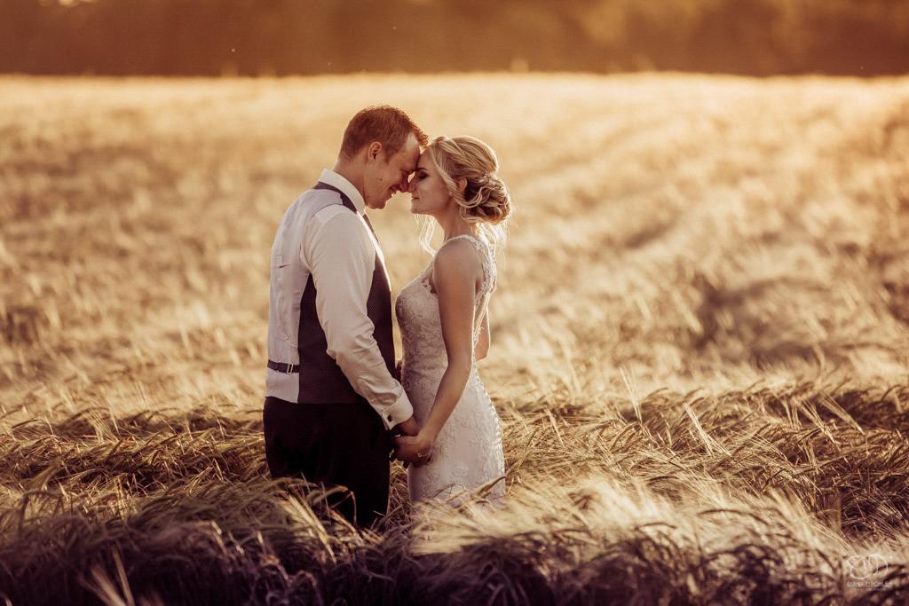 Brautpaar im Feld in tollem Licht bei Sonnenuntergang lachend Schwarzweissfoto / Hochzeitsfotos