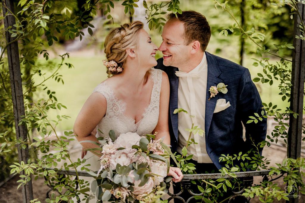 Brautpaar lacht im Pavillon zwischen Blättern im Frühling bei Hochzeit im Kraichgau Hochzeitsfotograf Karlsruhe