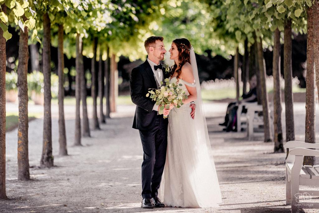 Brautpaar auf einer Allee zwischen Bäumen am Schloss Favorite schaut sich an