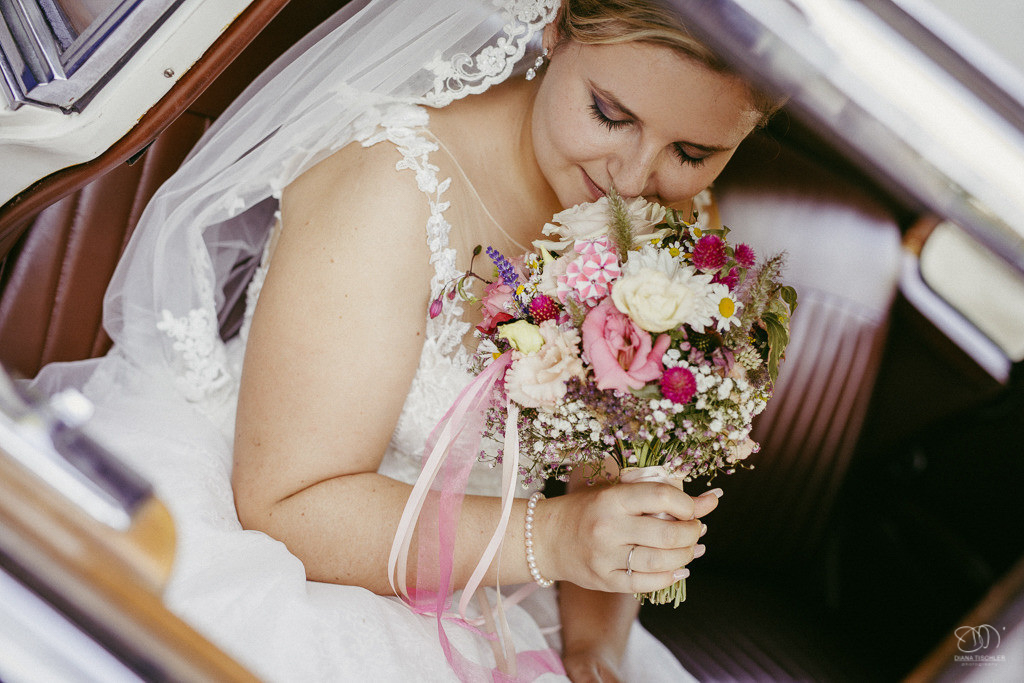 Braut mit Brautstrauss im Oldtimer