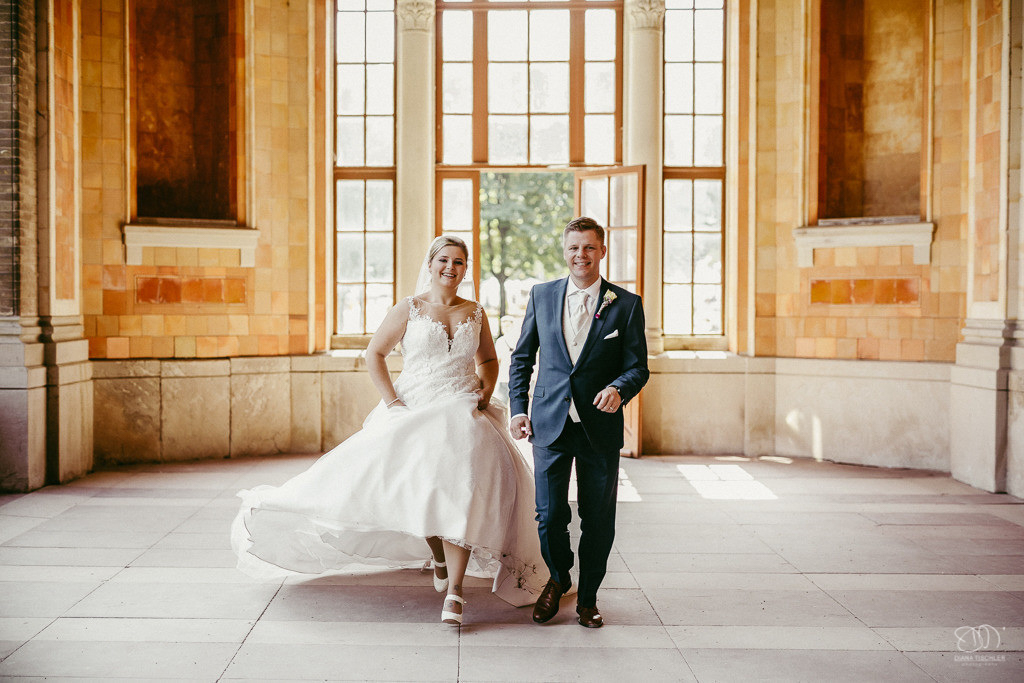 Brautpaar glücklich in der Trinkhalle in Baden-Baden rennt auf den Fotografen zu
