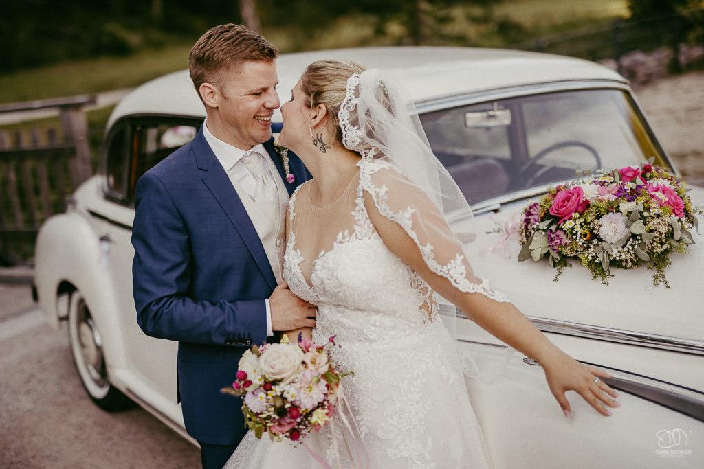 Brautpaar am Oldtimer küsst sich fast