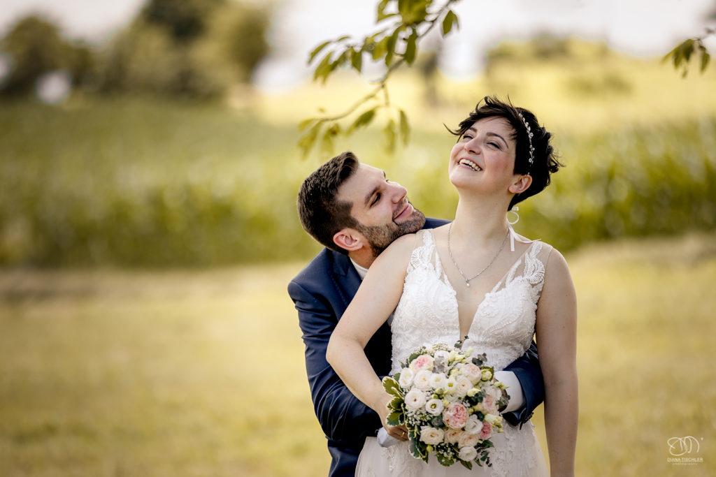 Brautpaar albert herum lachend unter Bäumen auf sommerlicher Wiese / Hochzeitsfotograf buchen