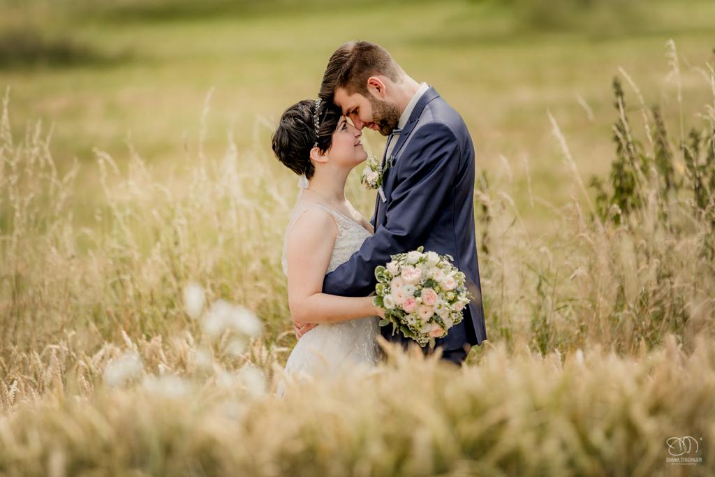Brautpaar innig romantisch im Kornfeld auf Wiesen im Sommer / Hochzeitsfotograf buchen