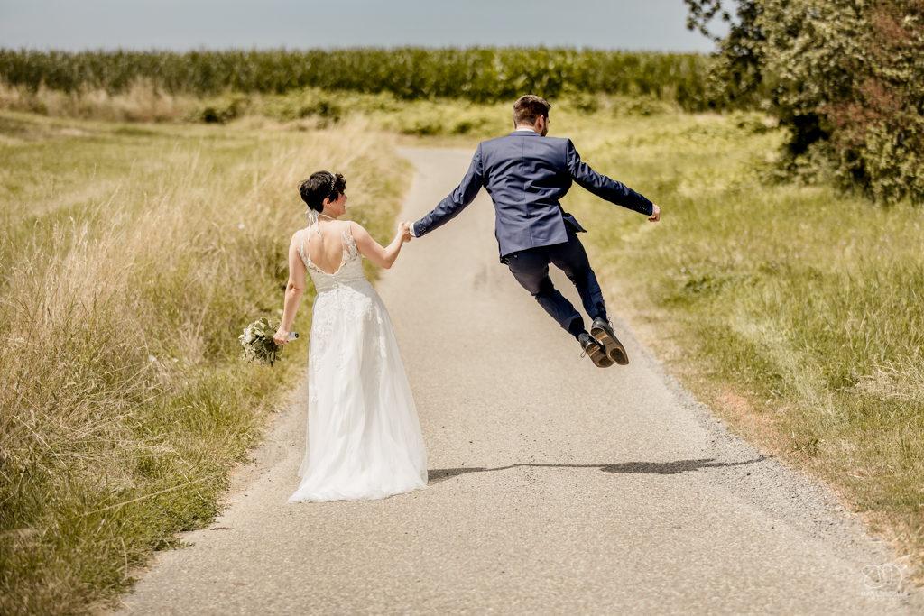 Brautpaar geht zusammen einen Weg durch Felder und Natur Bräutigam springt Hochzeitsfotograf