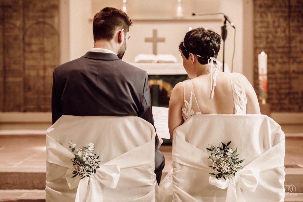 Brautpaar von hinten mit Altar und auf geschmückten Stühlen Hochzeitsfotograf Palmbach