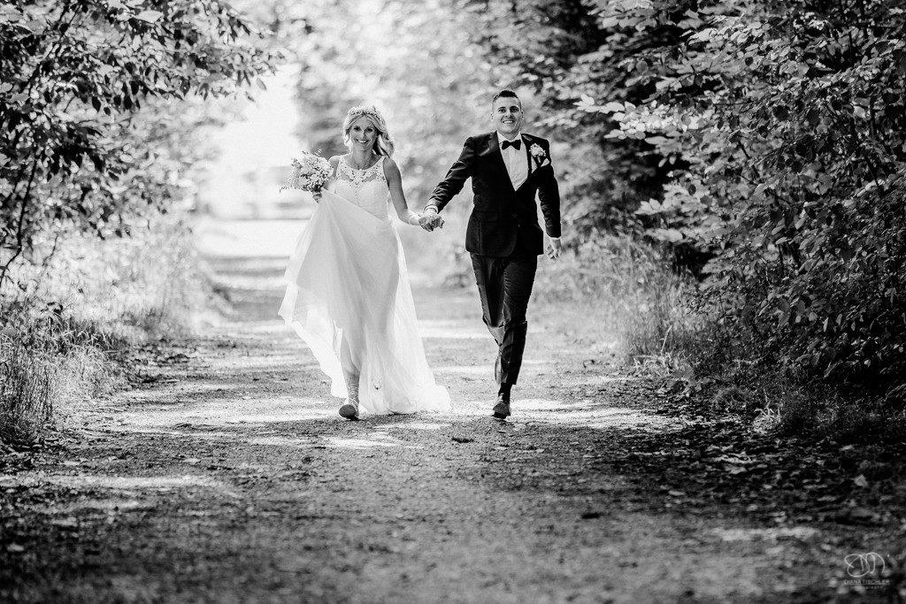 Brautpaar in der Natur rennt auf Waldweg auf die Fotografin zu Schwarzweissfoto
