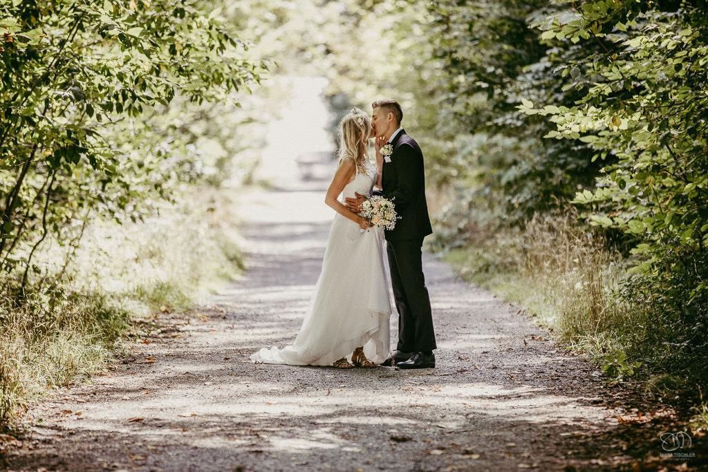 Brautpaar in der Natur küsst sich auf Waldweg Leistungen Hochzeitsfotograf Stuttgart