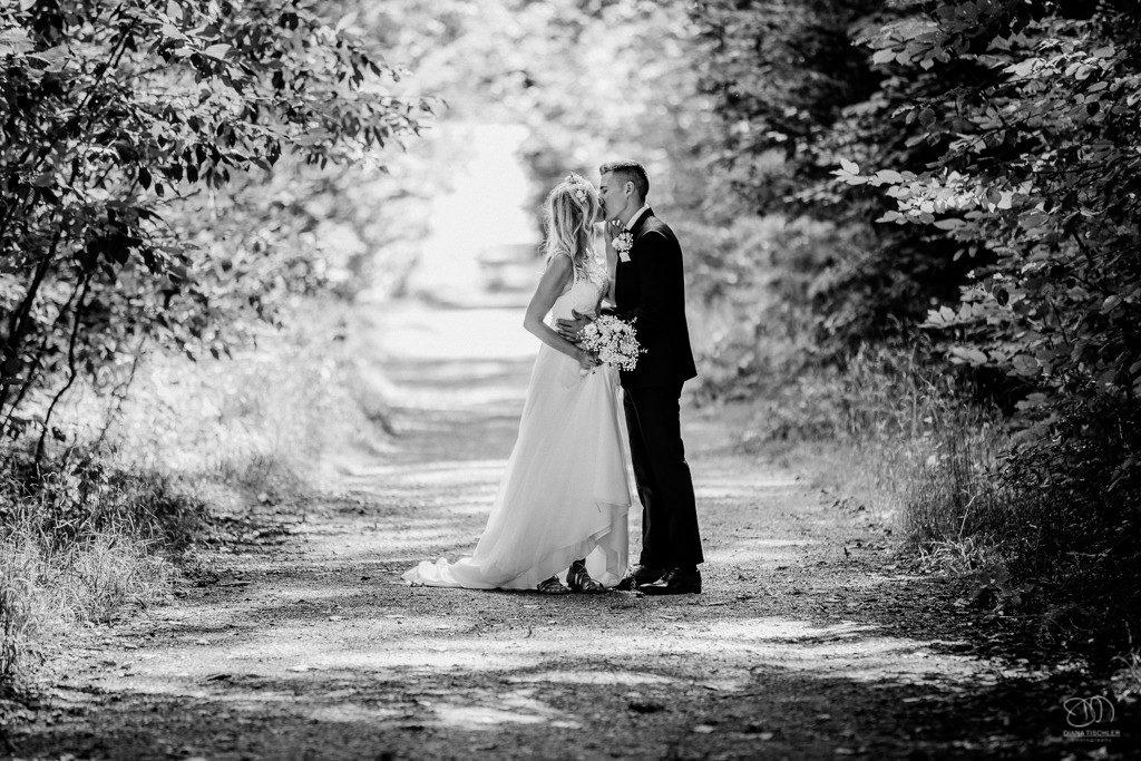 Brautpaar in der Natur küsst sich auf Waldweg Schwarzweissbild
