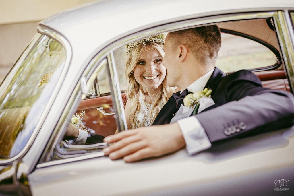 Brautpaar im Oldtimer lacht sich an Leistungen Hochzeitsfotograf Stuttgart
