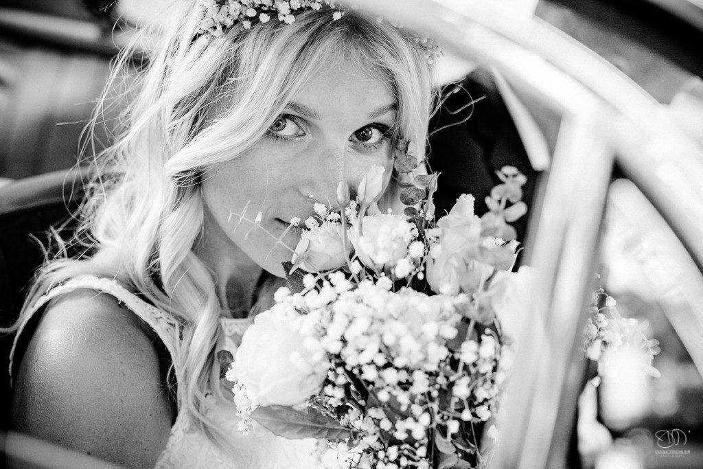 Braut mit Brautstrauss im Oldtimer schaut in die Kamera Schwarzweissfoto / Hochzeitsfotograf Stuttgart