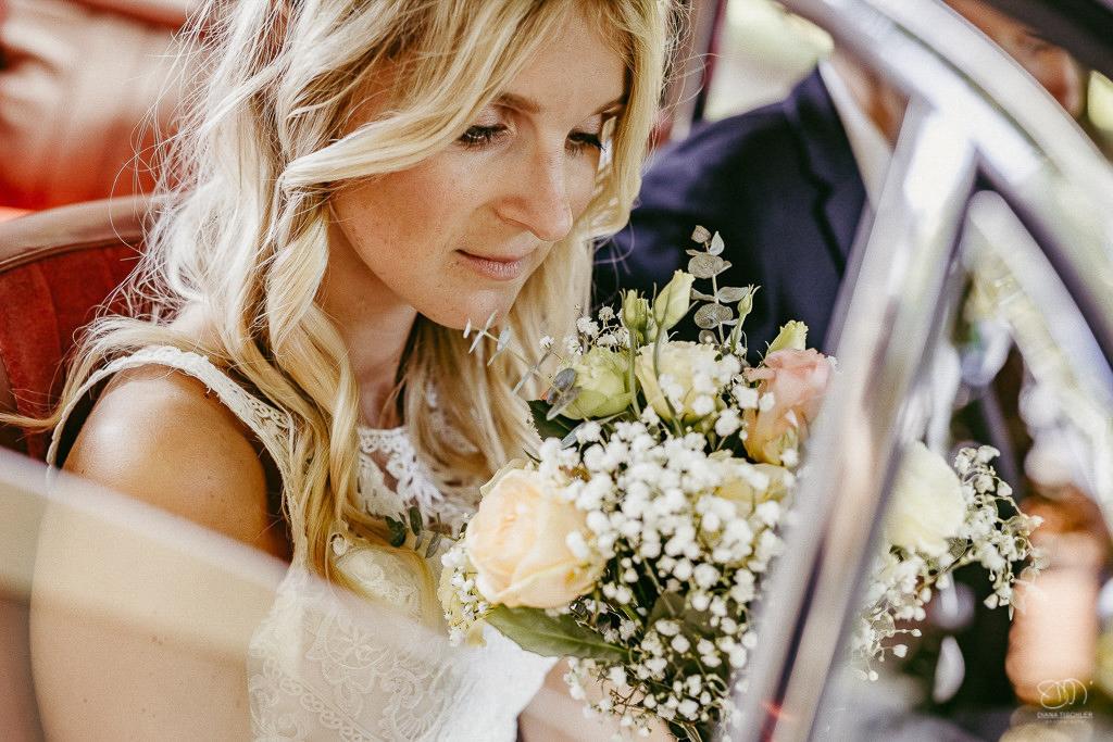 Braut mit Brautstrauss im Oldtimer Leistungen Hochzeitsfotograf