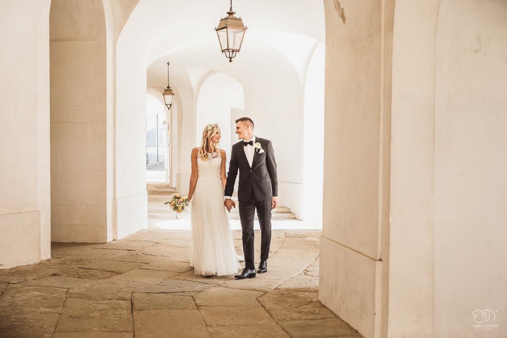 Brautpaar am Schloss Solitude unter den Arkaden Hand in Hand Leistungen Hochzeitsfotograf