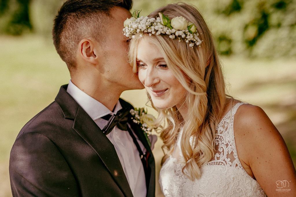Brautpaar flüstert sich Geheimnisse zu Leistungen Hochzeitsfotograf