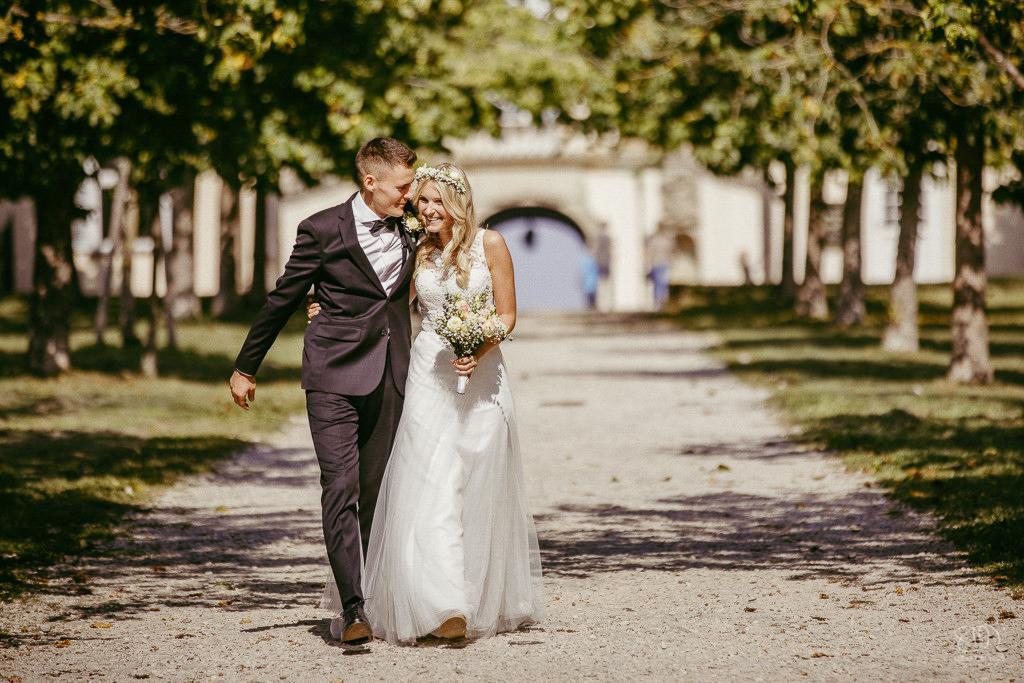 süßes Brautpaar auf dem Weg beim Schloss Solitude läuft lachend auf den Fotografen zu Leistungen Hochzeitsfotograf Stuttgart