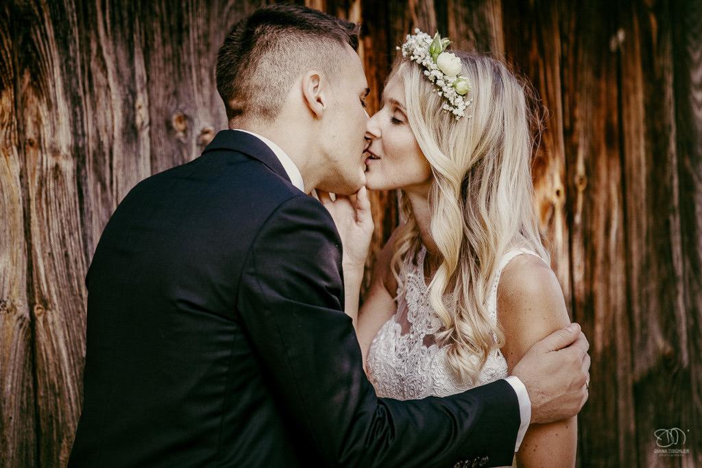 süßes Brautpaar küsst sich an Holzwand Leistungen Hochzeitsfotograf